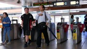 Movimiento de la gente que camina con la zona de paga del precio y que golpea ligeramente su tarjeta para tomar el MRT