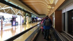 Movimiento de la gente que camina y que pasa tiendas de regalos dentro del aeropuerto de Taiwán