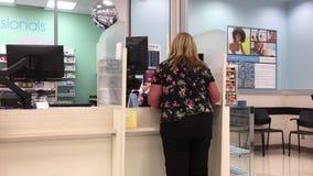 Movimiento de la gente que coge para su medicina en la sección de la farmacia