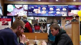 Movimiento de la gente que come la hamburguesa y que charla con el amigo metrajes