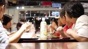 Movimiento de la gente que come las comidas en el área de la zona de restaurantes