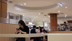 Movimiento de la gente que come las comidas y que juega el teléfono elegante en el área de la zona de restaurantes almacen de metraje de vídeo