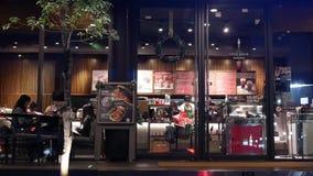 Movimiento de la gente que goza del café dentro del café de Starbucks en la noche