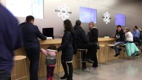 Movimiento de la gente que habla con el trabajador en la barra del genio dentro del Apple Store