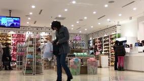 Movimiento de la gente que hace compras en artículo en venta en la tienda japonesa de la marca del diseñador