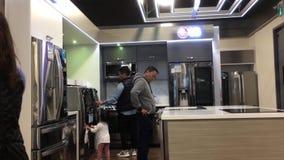 Movimiento de la gente que intenta un nuevo refrigerador dentro de la tienda electrónica metrajes