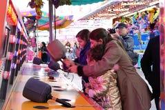 Movimiento de la gente que juega al juego del porrazo en el carnaval de las diversiones de la costa oeste Fotografía de archivo