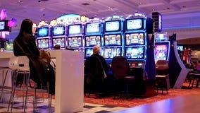 Movimiento de la gente que juega la máquina tragaperras y que se divierte dentro del casino almacen de metraje de vídeo
