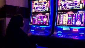 Movimiento de la gente que juega la m?quina tragaperras dentro del casino metrajes