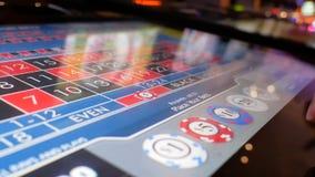 Movimiento de la gente que juega la ruleta del casino en la máquina con la bola de giro de la reflexión en la pantalla