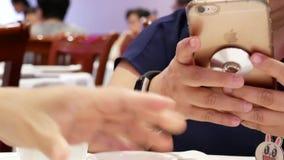 Movimiento de la gente que lee el mensaje en iphone y que vierte té caliente