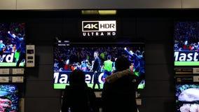 Movimiento de la gente que mira la nueva TV dentro de la tienda de Best Buy almacen de video