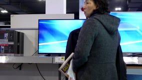 Movimiento de la gente que mira la nueva TV dentro de la tienda de Best Buy metrajes