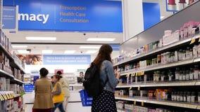 Movimiento de la gente que toma la comida sana y que coge para su medicina en la sección de la farmacia