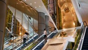 Movimiento de la gente que toma la escalera móvil dentro del hotel de Grand Hyatt