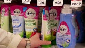 Movimiento de la gente que toma la crema del retiro del pelo de Veet