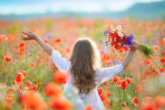 Movimiento de la muchacha del niño a través del campo floreciente con las flores salvajes rojas fotografía de archivo