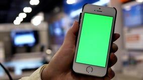 Movimiento de la mujer que celebra el teléfono de pantalla verde con la gente TV que hace compras