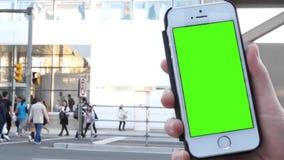 Movimiento de la mujer que celebra el teléfono de pantalla verde con la calle que cruza de la gente para tomar el skytrain almacen de video