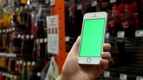 Movimiento de la mujer que celebra iphone verde de la pantalla con las herramientas de la exhibición almacen de metraje de vídeo