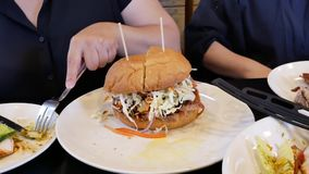 Movimiento de la mujer que come la hamburguesa en el restaurante chino almacen de video