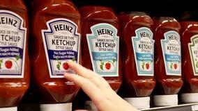 Movimiento de la mujer que compra Heinz salsa de tomate baja del sodio