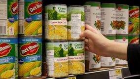 Movimiento de la mujer que compra maíz poner crema gigante verde del estilo