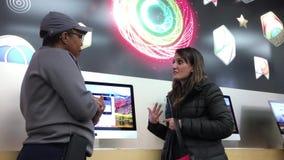 Movimiento de la mujer que hace preguntas acerca de iMac dentro de Apple Store almacen de video