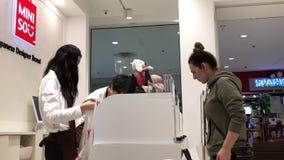 Movimiento de la mujer que paga la tarjeta de crédito en el contador de pago y envío en la tienda japonesa de la marca del diseña