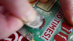 Movimiento de la mujer que rasguña el boleto de lotería en la sección de la prima almacen de video