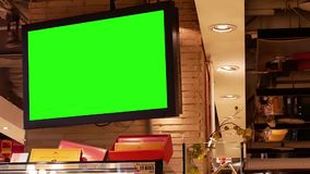 Movimiento de la pantalla verde grande TV en la pared dentro de la alameda de compras