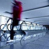 Movimiento de la persona en pasillo gris con las escaleras móviles Imagen de archivo