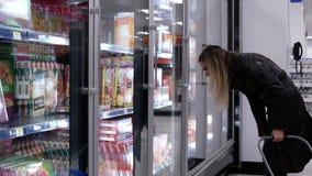 Movimiento de la pizza de la compra de la mujer dentro de la tienda de Walmart
