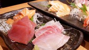Movimiento de la placa deliciosa de los salmones de la rebanada y del sashimi crudos del atún almacen de metraje de vídeo