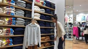 Movimiento de la ropa plegable del trabajador en el estante de la venta dentro de la tienda del uniqlo metrajes