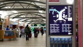 Movimiento de la señal y de los pasajeros de dirección con equipaje dentro del aeropuerto de YVR almacen de video