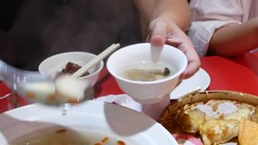 Movimiento de la seta blanca de colada de la gente y de la sopa wolfberry en el cuenco dentro del restaurante chino metrajes