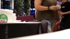 Movimiento de la tabla de la limpieza del trabajador después del cliente que deja la tabla
