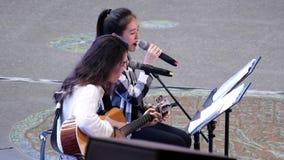 Movimiento de las chicas jóvenes que cantan y que tocan la guitarra en parque natural almacen de metraje de vídeo