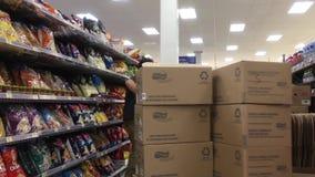 Movimiento de las galletas de la media del trabajador en el estante de exhibición metrajes
