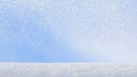 Movimiento de las nevadas del copo de nieve del invierno en fondos de un cielo azul
