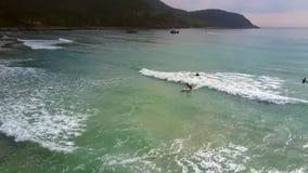 Movimiento de las personas que practica surf que cogen ondas a las muchachas en la playa metrajes