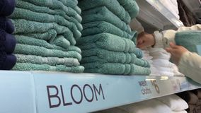 Movimiento de las toallas de mano de compra de la mujer dentro del superstore almacen de metraje de vídeo