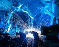 Movimiento de los robots de soldadura en una fábrica del coche Imagenes de archivo