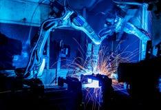 Movimiento de los robots de soldadura en una fábrica del coche Fotos de archivo libres de regalías