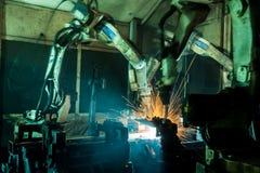 Movimiento de los robots de soldadura en una fábrica del coche Fotografía de archivo