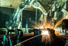 Movimiento de los robots de soldadura en una fábrica del coche Foto de archivo