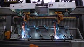 Movimiento de los robots de soldadura en fábrica del coche escena Movimiento del robot al soldar con autógena con las chispas en  almacen de video