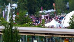 Movimiento de los viajeros que toman el skytrain y de la gente que celebra el día de Canadá en el parque almacen de video