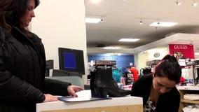 Movimiento de los zapatos de compra y de pagar de la mujer la tarjeta de crédito almacen de metraje de vídeo